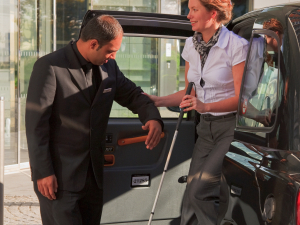 A partially sighted lady is helped into a taxi; Copyright: Visit Britain Images