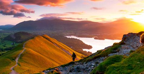 Sunrise on Catbells Mountain, The Lake District, Cumbria, England. Hiker walking along a path on the mountain ridge.