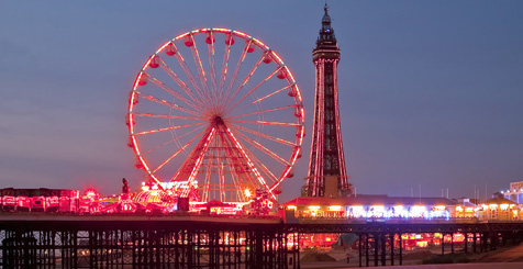 Image of a fairground wheel lit up at night