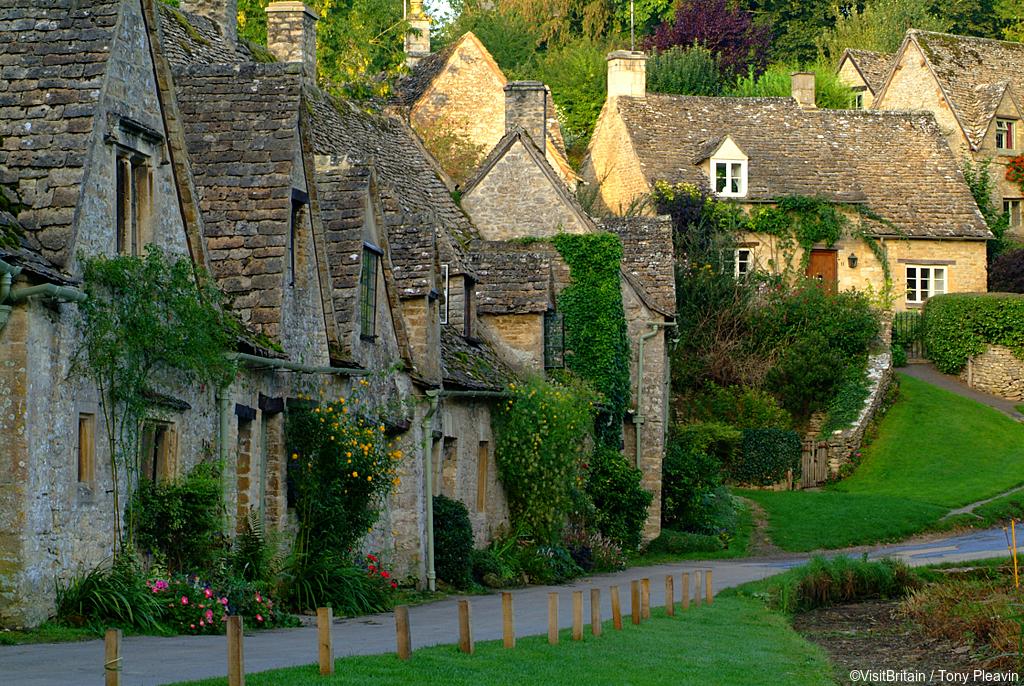 Row of quaint stone cottages in the Cotswold village of Bibury, Bibury, Gloucestershire, England.
