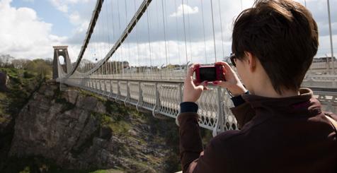 A woman taking a photo of Clifton Bridge