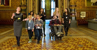 A group, including a man in a power wheelchair, being taken on a tour of the Houses of Parliament ©  VisitEngland Luke Rogers