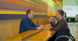 A man in a wheelchair having a cup of coffee with a friend (c) VisitEngland/VisitBritain/Pawel Libera