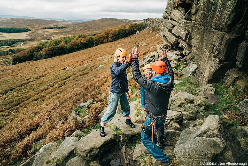 Three people in climbing gear, two women and a man, at Stanage Edge, Peak District, Derbyshire, England.