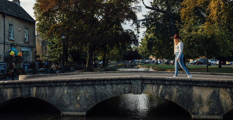 Blond woman wearing hat and jeans walking on bridge across river in Bourton on the Water, Cotswolds, Gloucestershire