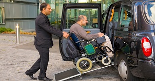 A staff member helps a man in a wheelchair into a taxi © VisitEngland/VisitBritain Pawel Libera