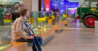 A man with crutches sitting down in a museum © VisitEngland/VisitBritain Pawel Libera