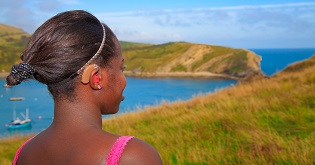 A woman wearing a hearing aid looks out over a green landscape © VisitEngland/VisitBritain Pawel Libera