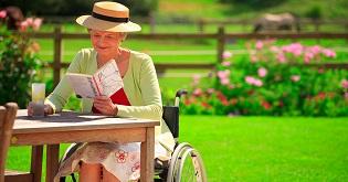A woman in a wheelchair reading in a garden