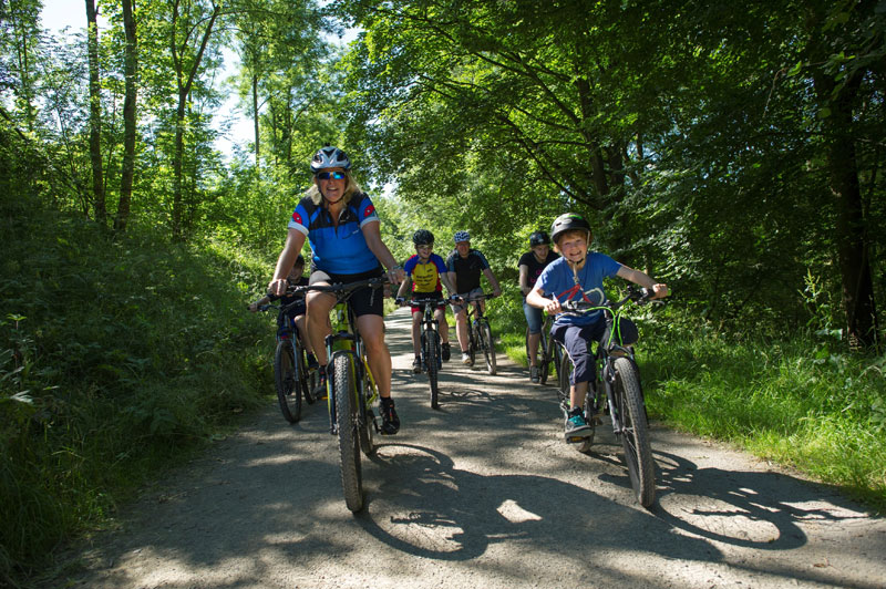 A family cycle past Dalby Forest's towering green trees in North Yorkshire