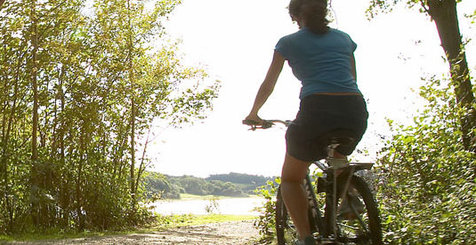 A lady cycling in the countryside.
