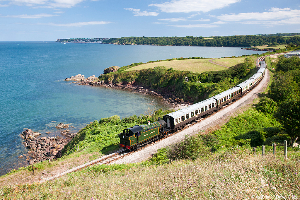 Steam train on the Dartmouth Steam Railway line, approaching Churston running along the coastline.