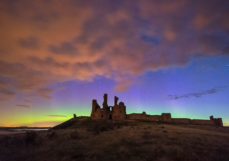 The green and purple hues of the northern lights illuminate the sky behind Dunstanburgh Castle