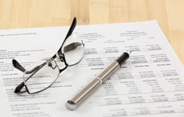 Image of spreadsheet with spectacles and pen