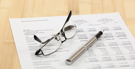 Image of a spreadsheet with glasses and pen