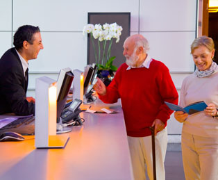 Elderly couple being served at a hotel reception desk