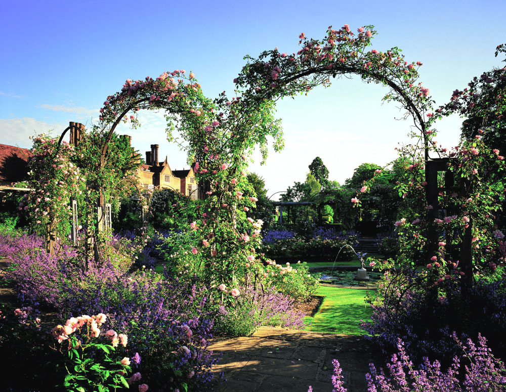 View of the garden with arches and flowerbeds at Great Fosters in Surrey