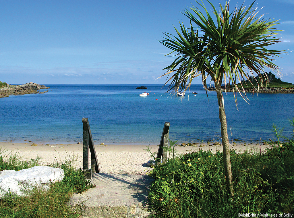 St Mary's Old Town Beach on the Isle of Scilly under a clear blue sky.