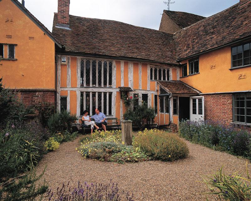 A couple sit in the back garden of a original Tudor house in Lavenham