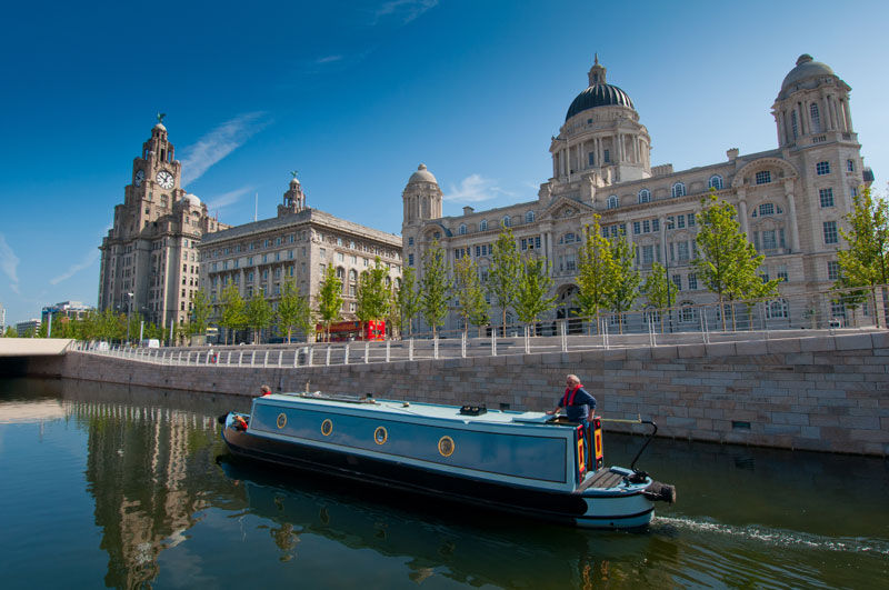 A canal boat in front of the Three Graces at the Pier Head, Liverpool