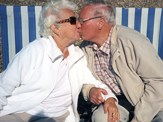 Couple kissing on deckchairs