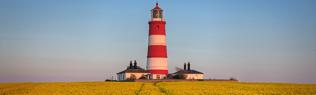 Early morning light on the red and white striped lighthouse at Happisburgh on the north east Norfolk coast. Rape seed flowering crop in the fields