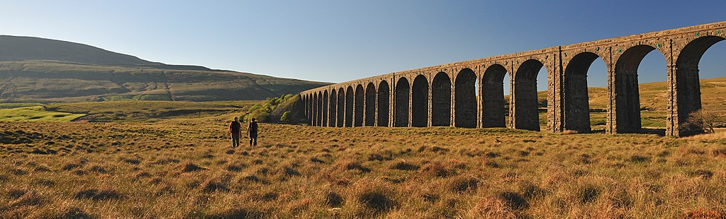 Two people on the path towards the historic Ribblehead Viaduct, a railway viaduct with 24 arches, built in 1870 across the Ribble Valley, at Whernside. The Settle-Carlisle railway line