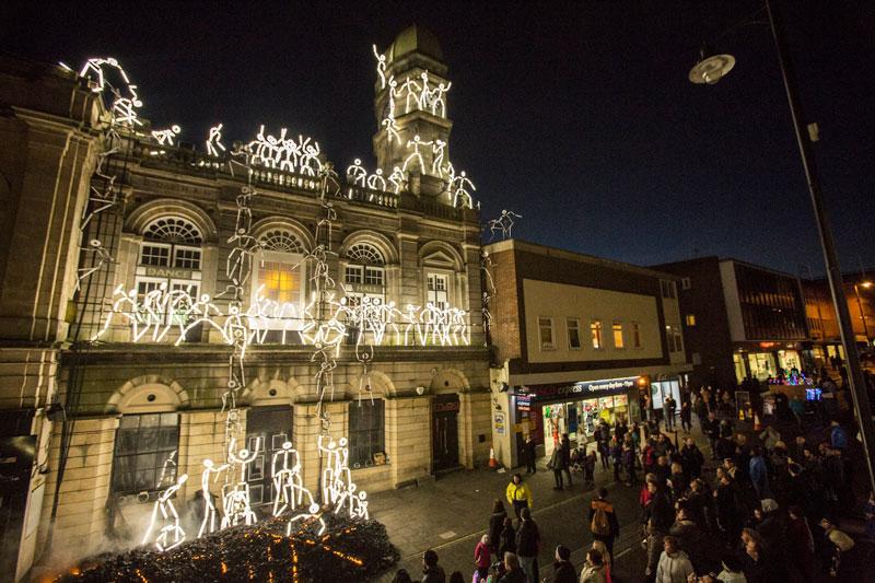 An art installation of illuminated matchstick men climbing a building in Durham