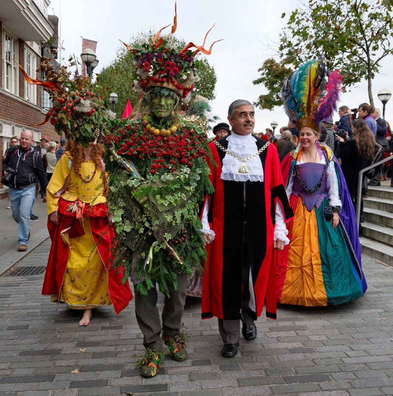 The Berry Man, bedecked with foliage, and the Mayor of Southwark parade along the River Thames