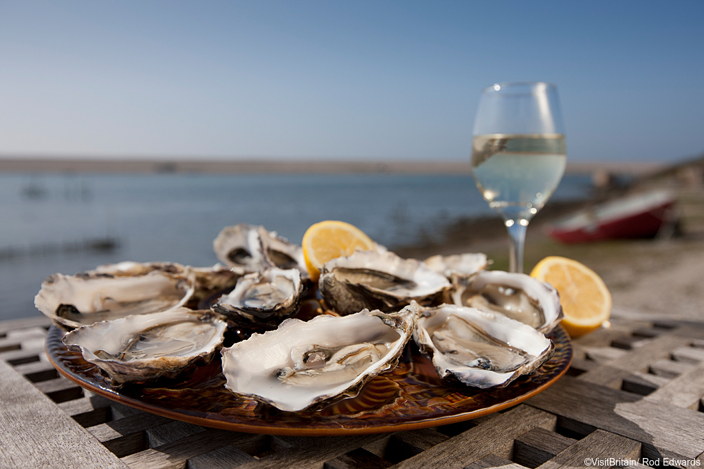 A platter of open shucked oysters with garnish of fresh lemons. A glass of chilled white wine. View out over the beach and sea.