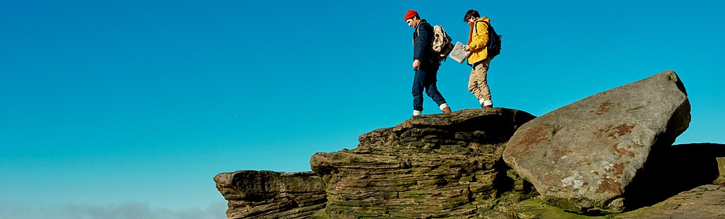 A couple, man and woman, walking along the edge of the cliff at Stanage Edge in the Peak District National Park. Bright blue sky
