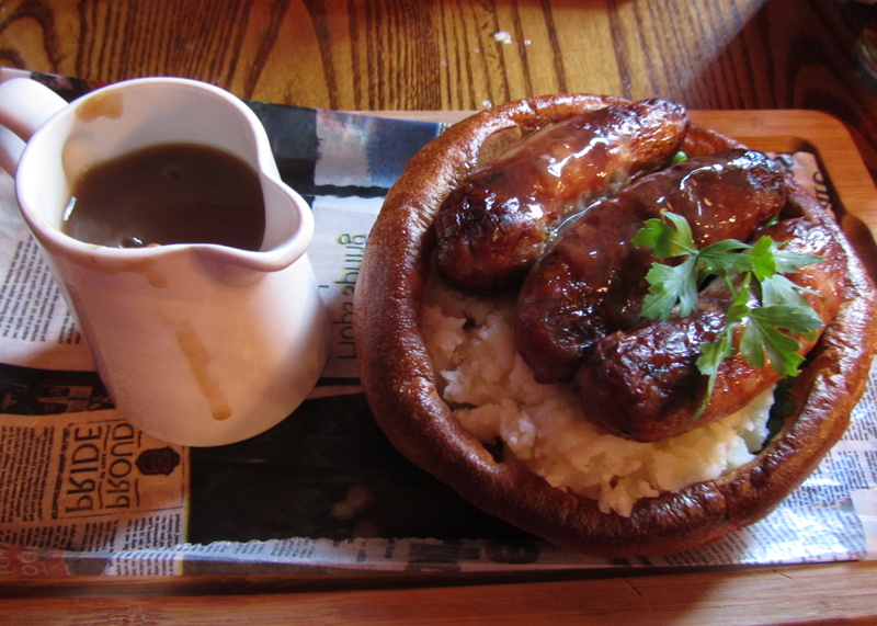 Sausage and mash in a Yorkshire pudding with a jug of gravy