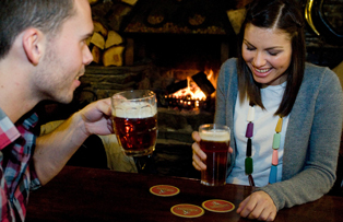 A couple in a pub drinking ale by the fire