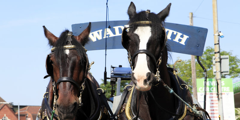 Horses pull a cart to the Wadworth Brewery