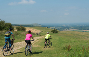 Three people cycling in rural Brighton
