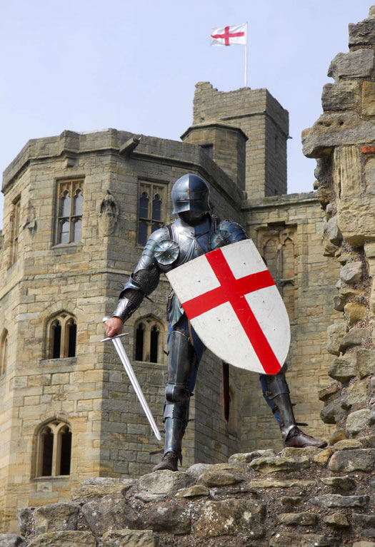 A knight in armour holding a St George's Cross shield stands in front of Warkworth Castle