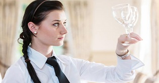 A waitress holds up a wine glass to check it's polished (c) Alex Hare