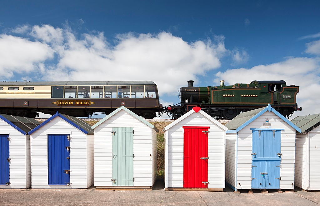 A steam train passes a row of beach huts in England.