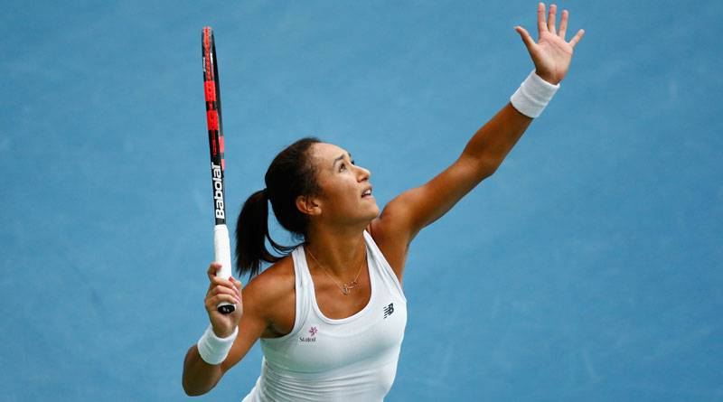 A female tennis player about to serve