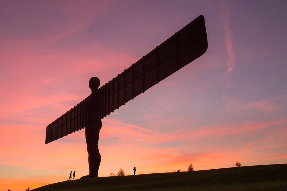 The wings of the Angel of the North stretch across a pink sky