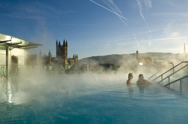 A couple take a dip in the blue pool of Thermae Spa while surrounded by mist