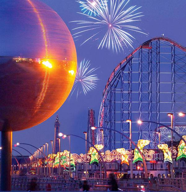 A view of the famous mirror ball landmark upclose,  illuminations lining the promenade and fireworks in the distance