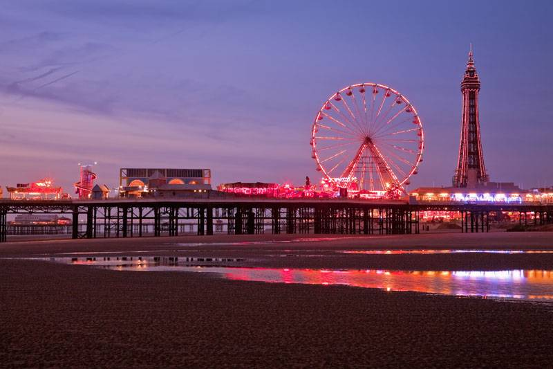 Blackpool's promenade lit up in red during the evening