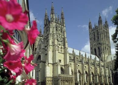 Canterbury Cathedral in the sunshine with petunia flowers in foreground and blue skies VE12365 389x280 (c) VisitEngland