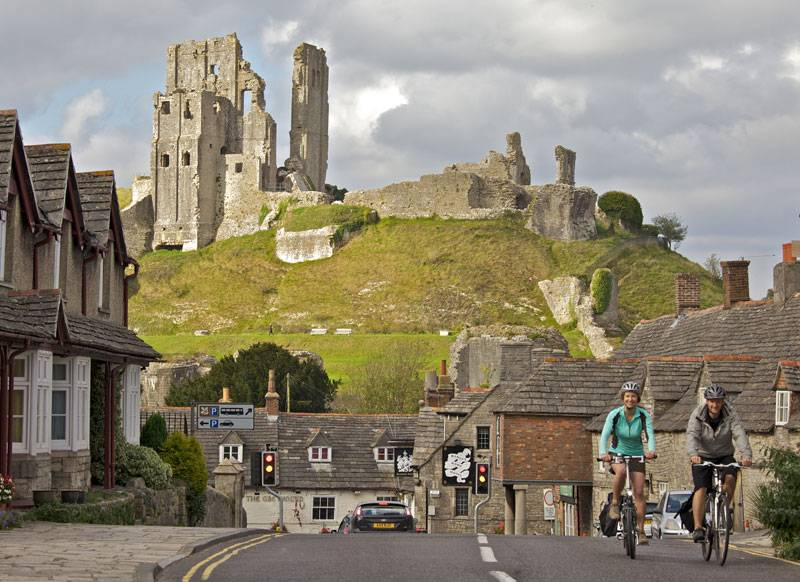 Cyclists pause on a cottage-lined street with Corfe Castle in the background