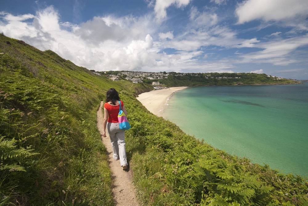 A woman strolls along a grass-flanked coastal path next to teal-coloured water in Cornwall