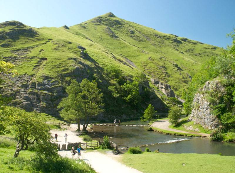 Walkers hop over the Dovedale stepping stones with a luscious peak in the background