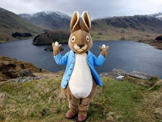 Peter Rabbit stands in front of a Bowness-on-Windermere in Cumbria
