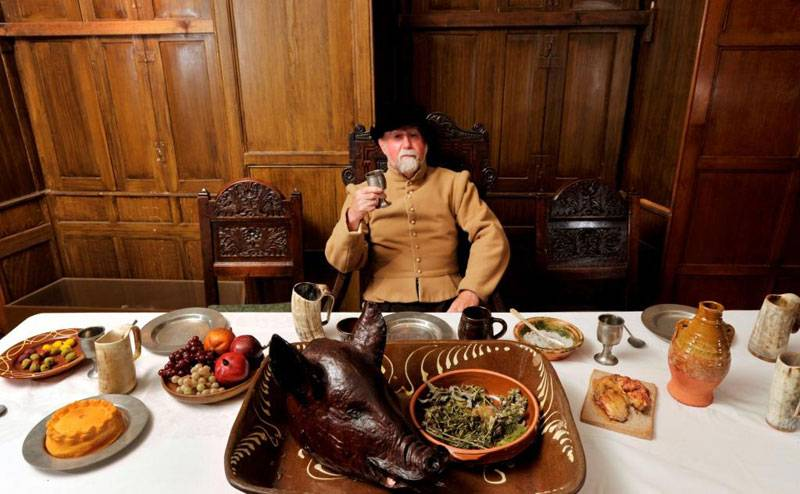 A costumed character sits in front of a tudor feast at the Elizabethan House