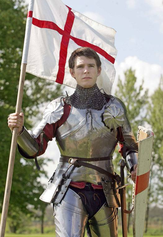 A man dressed as St George wearing a suit of armour and holding an English flag